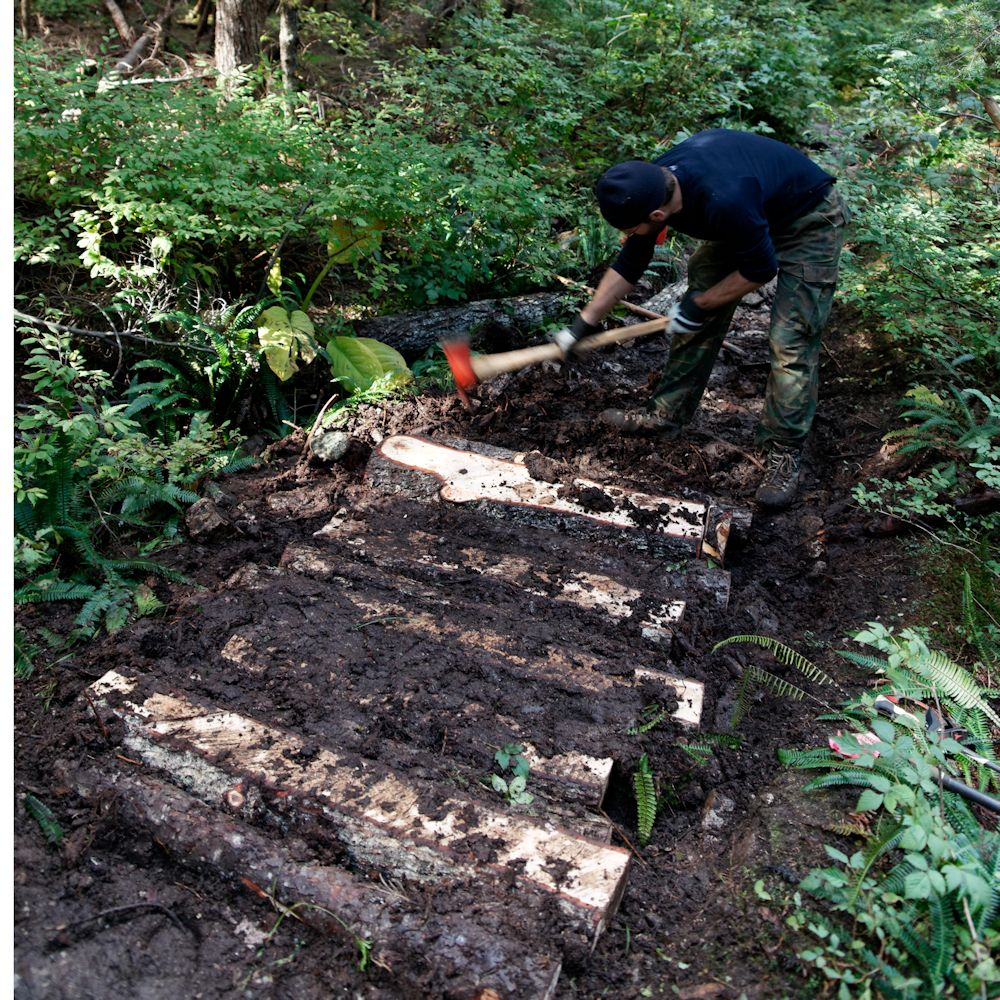 Alexis works on section of trail corduroy